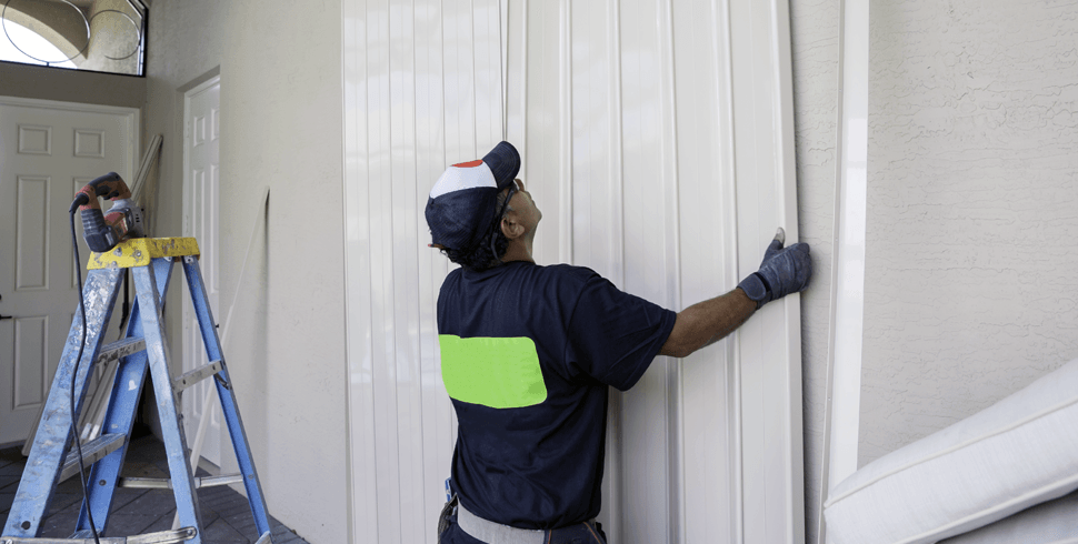 Man putting up shutters for storm preparation