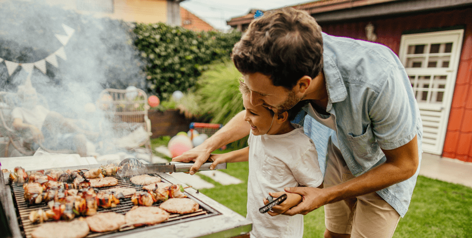 Father and son grilling burgers and kabobs outside