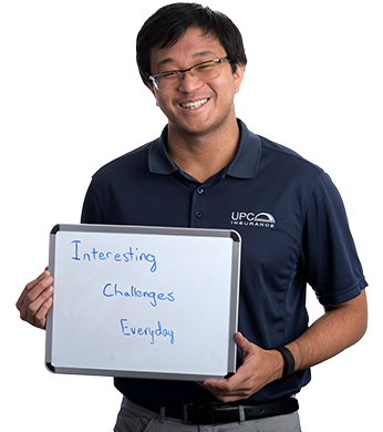 Jay-Yun Wang holding a sign which reads 'Interesting Challenges Everyday